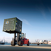 A Linde forklift truck lifting a shipping container whilst working on the Southampton dockside.
