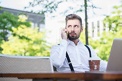 Businessman talking on mobile phone in outdoor cafe, Munich, Bavaria, Germany