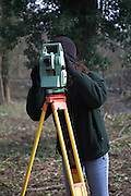 Woman surveyor using theodolite