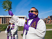 "05 APRIL 2020 - DES MOINES, IOWA:  Rev. RUSSELL LACKEY leads a prayer during a drive through Palm Sunday service sponsored by Luther Memorial Church on the campus of Grand View University in Des Moines. About 150 people attended the service. They remained in their cars while the ministers read a short passage from the Bible, handed out palms and blessed them. On Sunday, 05 April, Iowa reported 868 confirmed cases of the Novel Coronavirus (SARS-CoV-2) and COVID-19. There have been 22 deaths attributed to COVID-19 in Iowa. Restaurants, bars, movie theaters, places that draw crowds are closed until 30 April. The Governor has not ordered ""shelter in place"" but several Mayors, including the Mayor of Des Moines, have asked residents to stay in their homes for all but essential needs. People are being encouraged to practice ""social distancing"" and many businesses are requiring or encouraging employees to telecommute.        PHOTO BY JACK KURTZ"