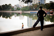 A Vietnamese man stands on the sidewalk watching a fisherman in Giang Vo lake, Hanoi, Vietnam, Southeast Asia