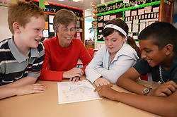 Teacher and pupils sitting around a desk talking in a classroom,