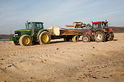 Tractor carrying salvaged timber washed up of beach from stricken cargo ship, Suffolk, England - January 2009