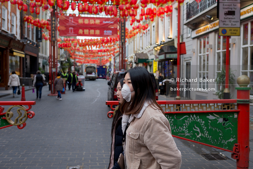 On the day that the UK government warns of 'draconian measures' to help control the spread of Coronavirus, a young woman wearing a protective face mask obscuring her face from any Coronavirus contact, crosses Gerrard Street with an uncovered friend in London's Chinatown, on 3rd March 2020, in London, England.