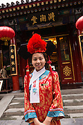 A young woman dressed in traditional Chinese costume at the Fangshan Imperial Restaurant welcome customers at Beihai Park in Beijing, China