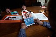 Nederland, Wijchen, 10-2-2020Een medewerkster, mobiel adviseur, van de Rabobank bezoekt ouderen thuis om bankzaken te regelen. Ze heeft een informatiepakket bij zich die door de overheid is samengesteld om ouderen advies te geven .Foto: Flip Franssen