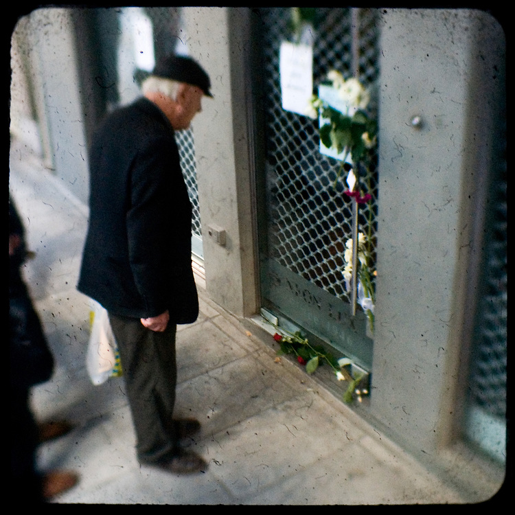 Flowers outside the closed shop of the mother of Alexandros Grigoropoulos. <br /> <br /> Following the murder of a 15 year old boy, Alexandros Grigoropoulos, by a policeman on 6 December 2008 widespread riots, protests and unrest followed lasting for several weeks and spreading beyond the capital and even overseas<br /> <br /> When I walked in the streets of my town the day after the riots I instantly forgot the image I had about Athens, that of a bustling, peaceful, energetic metropolis and in my mind came the old photographs from WWII, the civil war and the students uprising against the dictatorship. <br /> <br /> Thus I decided not to turn my digital camera straight to the destroyed buildings but to photograph through an old camera that worked as a filter, a barrier between me and the city.