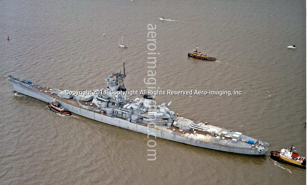 Aerial view of USS NewJersey final voyage up Delaware River, before decommissioned at Port of Camden in 1999
