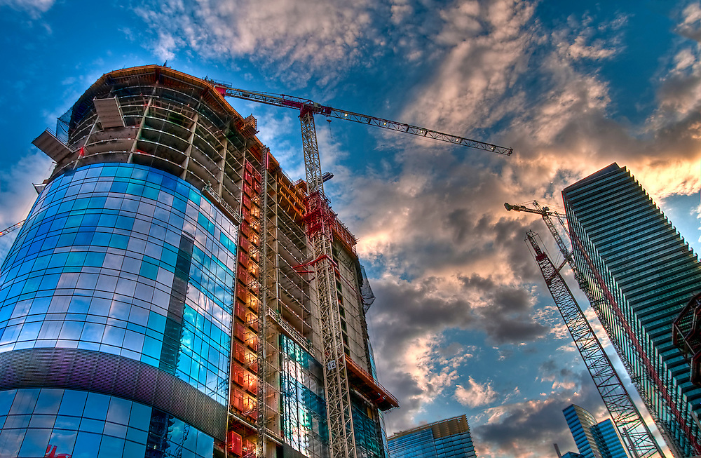 View of construction site with towers and crane.