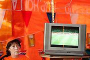 In een grote tent aan de Royaards van den Hamkade in de Utrechtse volkswijk Ondiep, de wijk waar Wesley Sneijder vandaan komt, kijkt een grote groep oranjesupporters naar de wedstrijd.<br /> <br /> A woman is watching the finals of the World Championship Soccer 2010 in a partytent in the Utrecht district Ondiep.