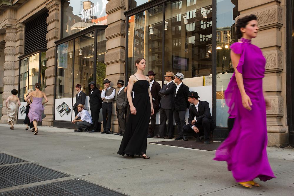 Women dancers stroll by the watching men.