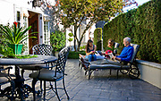 A trio of Portland homes where small front lawns have disappeared, transformed into functional courtyards.  This is Gayle & Larry Cheldelin's home at 1709 SW Montgomery Dr. in Portland. Their daughter, Jade, joins them on their courtyard patio.   Photo by Randy L. Rasmussen/Staff Photographer