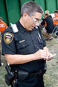 Policeman making notes. Special Olympics U of M Bierman Athletic Complex. Minneapolis Minnesota USA