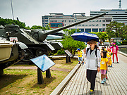 08 JUNE 2018 - SEOUL, SOUTH KOREA: A school group walks past a static display of armor and artillery at the War Memorial of Korea in Seoul, South Korea. With the near constant threat of invasion from North Korea, many South Koreans take great pride in the ability of their armed forces. Some observers believe there is a possibility that a peace agreement between South and North Korea could be signed following the Trump/Kim summit in Singapore. The War Memorial and museum opened in 1994 on the former site of the army headquarters to exhibit and memorialize the military history of Korea. When it opened in 1994 it was the largest building of its kind in the world. The museum features displays about the Korean War and many static displays of military equipment.    PHOTO BY JACK KURTZ