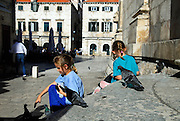 Two children (9 years old, 5 years old) feeding pigeons, Dubrovnik old town, Croatia
