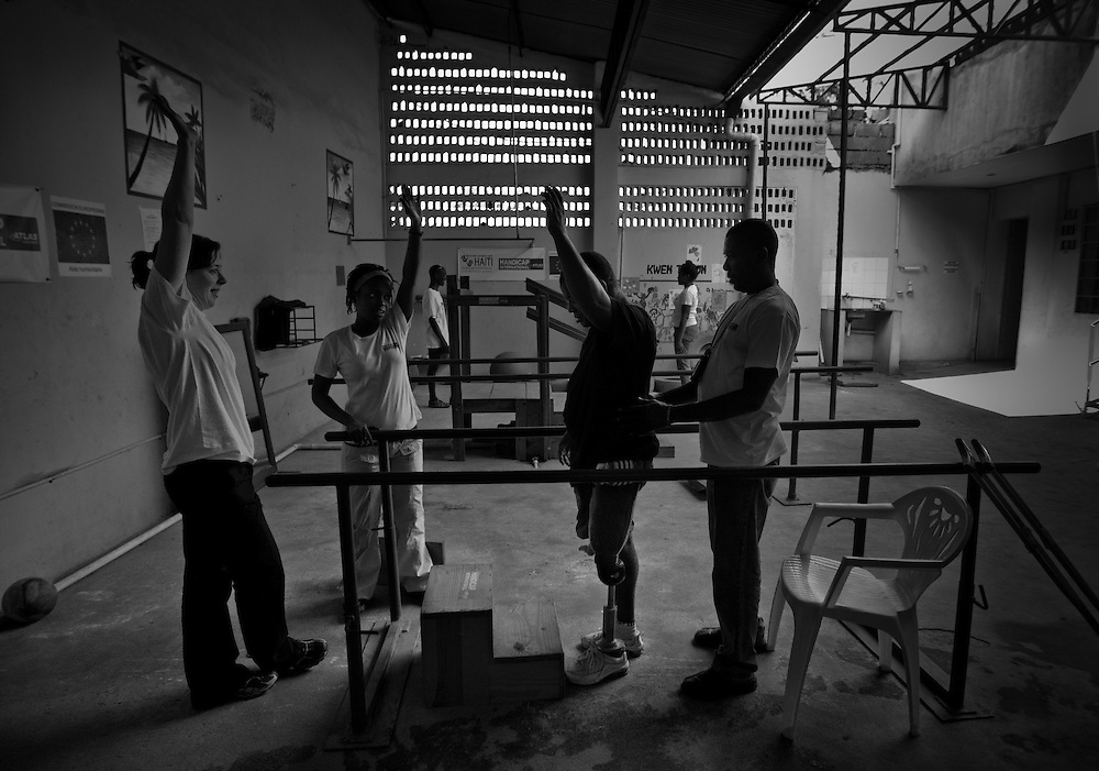 """Blane Zetienner, age 52, lost his leg from the earthquake, undergoes physical therapy at Healing Hands Haiti Clinic. <br /> <br /> Healing Hands Haiti (HHH) in Port Au Prince has been established for 12 years since 1999. Currently, HHH is constructing a new facility in Port Au Prince because their old clinic was destroyed from the earthquake.   HHH provides physical therapy, counseling, prosthetics, and support for free or very little cost to Haitians.  Their funding comes from private donations and organizations such as Handicap International, Mission Europeene Aide Humanitarian, International Committee of the Red Cross (ICRC), American Red Cross, Newman's Own, Direct Relief International (DRI), SOROS Open Society Foundation, and USAID which pays for employees, doctors, supplies, and facilities.  The motto of HHH is """"to serve the people of Haiti is to enable them to help themselves.""""   Thus, most of their employees are Haitians with very few foreign expats. Furthermore, HHH recruits and teaches young Haitian students prosthetic and orthotic skills and physical therapy in a specialized program that will enable them to earn a degree approved by World Health Organization."""