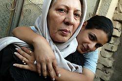 Alyaa Abdul Hassan Abbood, 23, a translator, hugs her mother, Baghdad, Iraq, Sept. 28, 2003. Abbood works with the U.S. military to mediate as Iraqi civilians come in to receive monetary compensation for damages done by American troops in Baghdad.