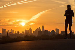 Primrose Hill, London, October 28th 2016. An early morning jogger  enjoys the cool morning air on Primrose Hill as the sun rises over London's skyline.