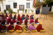 In a Punjabi rural school, children take exams sitting on mats on the open ground of the school yard amidst the remnants of a cold misty winter morning, India.