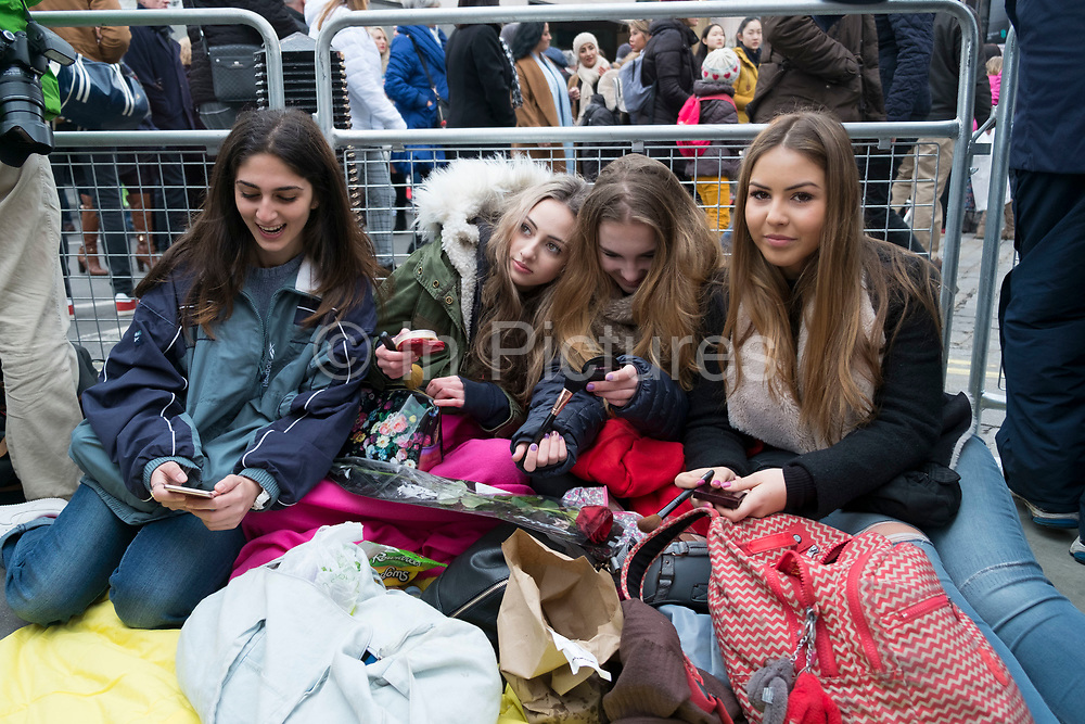 Girls waiting to see their favourite movie stars outside the BAFTA Awards ceremony in London, England, United Kingdom. Elena, Izzy, Bella and Azzurra doing their make up while they wait under blankets in the cold. Izzy has a red rose she hopes to give to Leonardo DiCaprio.