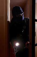 Een inbreker met bivakmuts en zaklantaarn.<br />