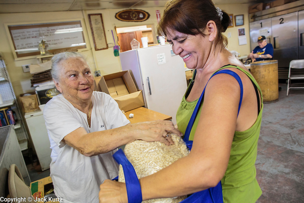 07 AUGUST 2012 - TOLLESON, AZ: AVIVA WININGER, left, a volunteer, helps a client with oatmeal at the food bank in Tolleson, AZ, about 15 miles west of Phoenix. The Tolleson food bank has been operating for more than 20 years. It used to serve mostly the families of migrant farm workers that worked the fields around Tolleson but in the early 2000's many of the farms were sold to real estate developers. Now the food bank serves both farm worker families and people who lost their homes in the real estate crash, that his Phoenix suburbs especially hard. More than 150 families a day are helped by the Tolleson food bank, an increase of more than 50% in the last five years.    PHOTO BY JACK KURTZ