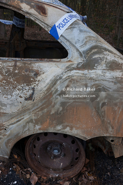 A burned-out car found abandoned by unknown vandals on 27th November 2016, in woodland near Hollingbourne, Kent, England.