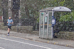 © Licensed to London News Pictures. 29/03/2020. Sheffield,UK.  A man jogs in an empty street during a heavy hail storm on Ecclesall Road  as takes his daily exercise in Sheffield. British Prime Minister Boris Johnson urges people to stay home and to go out only to buy food , medicines  and to do their daily exercise. Photo credit: Ioannis Alexopoulos /LNP