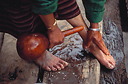 Sangay washes her feet with water from a gourd before attending a religious festival at the local temple in Shingkhey village. This is part of the two-day ceremony--or pujo--that is held every year to bless the village. To a continuous background of chanting, the monks fill the valley with long, slow, deep notes from their horns. Shingkhey, Bhutan. Published in Material World: A Global Family Portrait, page 79.