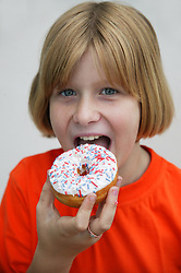 Portrait of a teenage girl eating a donut,