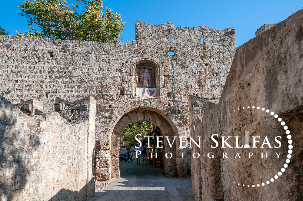 Rhodes. Greece. The arched stone gate of St Anthony inside the old walled medieval town of Rhodes. The old town is a UNESCO world heritage listed site and the best preserved, oldest and largest living medieval city in Europe. The 4km defensive walls were built by the Knights of St John during the 13th to 15th century to defend Western Europe against the expanding Ottoman Empire. Within the walls are a medieval warren of small alleyways and magnificent historical buildings. The island of Rhodes is the largest of the Dodecanese Island group and one of the most popular Greek Islands.