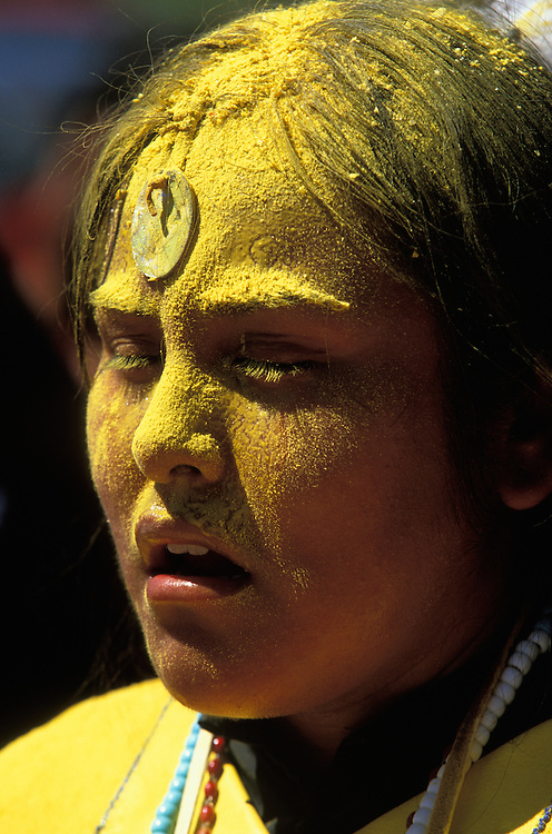 An Apache girl at her Sunrise Dance on the San Carlos Apache Reservation, Arizona, USA. The girl is covered with sacred yellow pollen from the cattail plant that has been applied as a blessing by the medicine man and her relatives. On her forehead  she wears an abalone shell, symbolising Changing Woman, a mythical female figure. The Sunrise Dance is an enactment of the Apache creation myth and during the rites the girl 'becomes' Changing Woman and comes into possession of her healing powers. The rites are also supposed to prepare the girl for adulthood and to give her a long and healthy life without material wants.