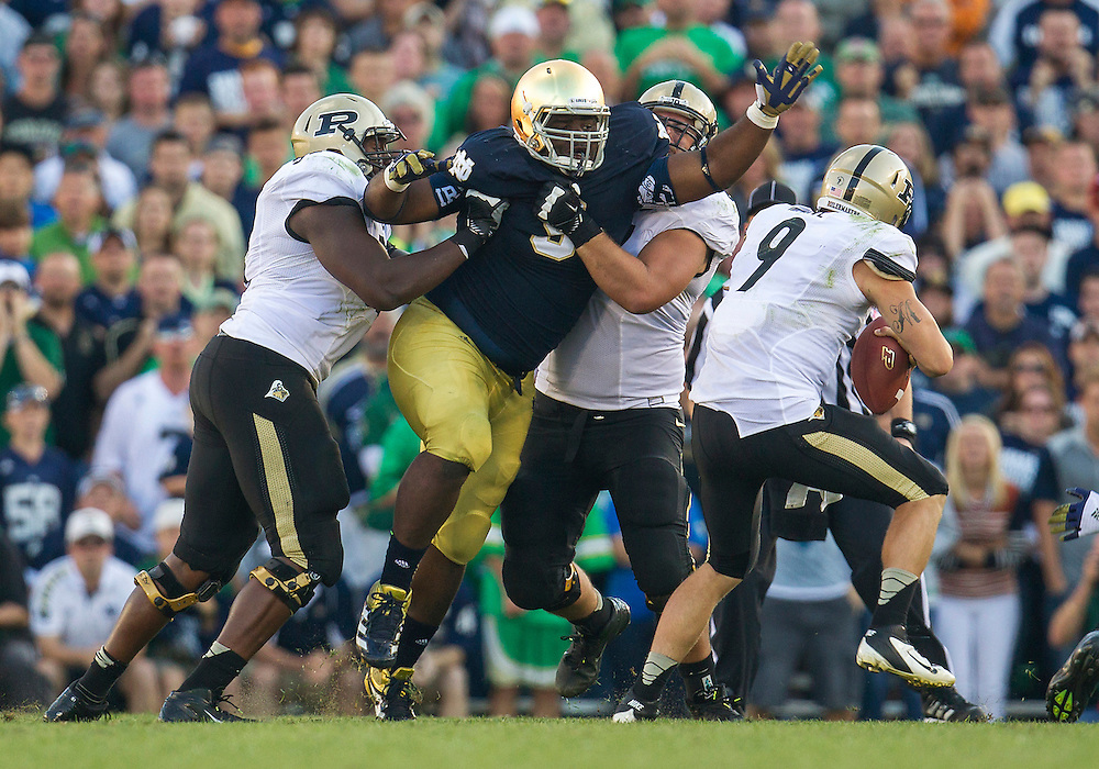 September 08, 2012:  Notre Dame nose guard Louis Nix III (9) breaks through the blocks to sack Purdue quarterback Robert Marve (9) during NCAA Football game action between the Notre Dame Fighting Irish and the Purdue Boilermakers at Notre Dame Stadium in South Bend, Indiana.  Notre Dame defeated Purdue 20-17.