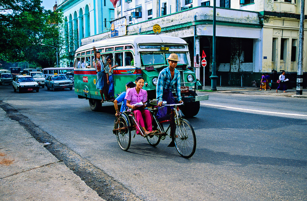 Bicycle taxi and public bus on Strand Road, Yangon (Rangoon), Burma (Myanmar)