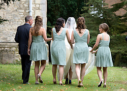 © London News Pictures. 14/09/2013.  Bridesmaids carry the brides dress as she enters the church with her father Jonathan Ashman.  The wedding of Euan Blair, Son of former British Prime Minister Tony Blair,  to Suzanne Ashman at All Saints Parish Church in Wotton Underwood, Buckinghamshire. The wedding was attended by Former British Prime minister Tony Blair and his wife Cherie Blair. Photo credit: Ben Cawthra/LNP
