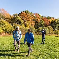 Three young men walk on a hilltop field in Amesbury, Massachusetts.