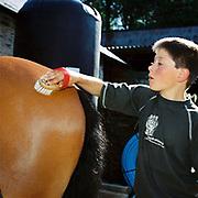 Exmoor hill farmer's son Giles Hawkins grooms his horse with a brush at Warren Farm, Simonsbath, Somerset, UK