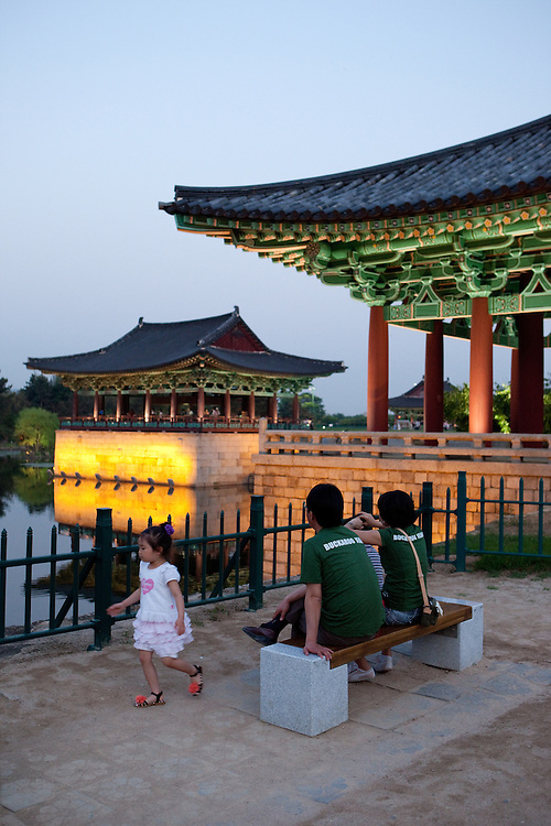 """Family during an evening at Anapji pond in the city of Gyeongju. Gyeongju was the capital of the ancient kingdom of Silla (57 BC - 935 AD) which ruled most of the Korean Peninsula between the 7th and 9th centuries. A vast number of archaeological sites and cultural properties from this period remain in the city. Gyeongju is often referred to as """"the museum without walls"""". / Gyeongju, South Korea, Republic of Korea, KOR, 20th of May 2010."""