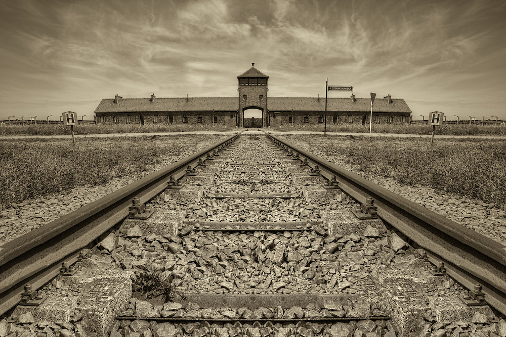 """The main entrance into Birkenau, also known as the Auschwitz II concentration camp. Beginning around the middle of May 1944, freight trains that were 40 to 50 cars long rolled through this gate, day and night, bringing thousands of Hungarian Jews to be gassed at the four Birkenau gas chambers. The prisoners called it the """"Gate of Death."""""""