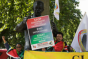 Windrush campaigners protest alongside the statue of Nelson Mandela in Parliament Square on 23rd June 2021 in London, United Kingdom. The campaigners, who marched from the Home Office to the House of Commons to deliver a letter, are calling for a new independent body, and not the Home Office, to administer the scheme intended by the government to compensate them for the violation of their rights. Many legal residents who came to the UK from the Caribbean lost their homes, jobs and other rights after having been targeted by the Home Office.