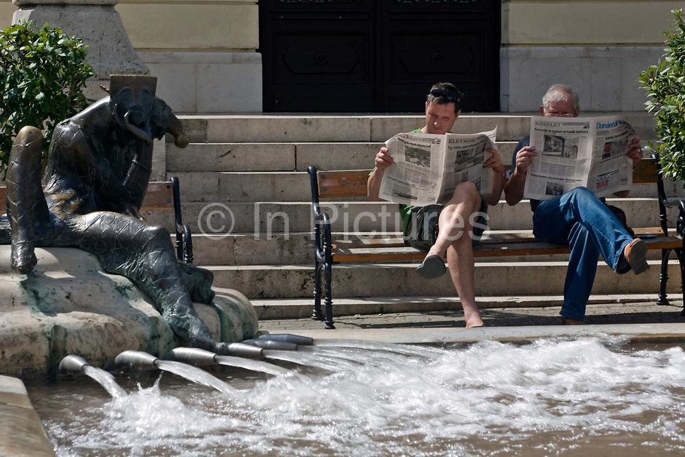Two men read a newspaper by a modernist fountain, Pec, Hungary.Pecs has been chosen as the 2010 European City of Culture. The city is on the southern slopes of the Mecsek Hills and has a sub-Mediterranean climate. Settled by Romans as Sopianae, it was a significant Christian settlement. Later conquered by the Ottomans, it has important Turkish architecture.