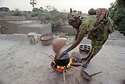 Fatoumata Toure stirs a pot of porridge on the roof of her home in the village of Kouakourou, Mali. The Natomo family lives in two mud brick houses in the village of Kouakourou, Mali, on the banks of the Niger River. They are grain traders and own a mango orchard. According to tradition Soumana is allowed to take up to four wives; he has two. Wives Pama and Fatoumata are partners in the family and care for their many children together. Material World Project.