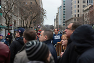 "A man wearing a ""Not My President"" shirt stands outside a barrier as others wait in line to pass through security to enter the inaugural parade route.<br />