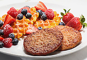 Sausage patties,waffles,fresh fruits in a plate