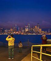 A Washington state DOT ferry provides a platform for a family of cell phone photographers filming the Seattle skyline at night in Elliot Bat of Puget Sound In Washington state, USA