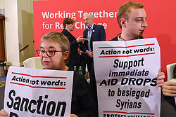 © Licensed to London News Pictures. 10/12/2016. London, UK. Labour leader and the leader of opposition JEREMY CORBYN and Shadow Foreign Secretary EMMA THORNBERRY are interrupted by 'Syria Solidarity UK' protesters whilst speaking on human rights at the Methodist Central Hall in Westminster, London on Saturday, 10 December 2016. Photo credit: Tolga Akmen/LNP