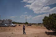 Resident Janet Bizoti walks near a compound of homes in Coyote Canyon Chapter in the Navajo Nation near Gallup, New Mexico. Bizoti grew up here, and this area's water has been heavily contaminated by uranium, which forces them to have to haul water from wells far away from their homes.