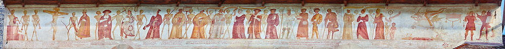 """The Church of San Vigilio in Pinzolo and its fresco paintings """"Dance of Death"""" painted by Simone Baschenis of Averaria in1539, Pinzolo, Trentino, Italy.<br /> <br /> The Mural opens on its left with a skeleton on the throne, bearing a sceptre and the crown and playing a bagpipe. These skeletons are playing the music which is the backdrop to """"Dance of Death"""" ( Danza macabra ) and suggests that they are playing with our fate on earth. <br /> <br /> The mural continues for another 21 meters with a long procession with 40 figures. To the right of the skeletons playing music is a depiction of the crucification. Christ is depicted on the cross with an arrow in him that has been fired by a skeleton with a bow. This suggests that because Christ was a man he suffered the fate of death as we all will. After Christ is a Pope also pierced by a spear, as are all the human figures in the mural. Next to the pope is a cardinal, a cleric and a monk all of whom have succumbed to the arrows of the skeletons. This tableau is a reminder to the hierarchy of the church that even they are not immune from death. The procession continues with a depiction of a king then nobility followed by knights and soldiers and a beggar man with no legs. Between each figure are skeletons holding bows and arrows, banners with writings on them or a shovel to dig a grave. After the beggar mad there are figures of women ending with a small skeleton and a cherub. To the far right a skeleton on a horse is riding into the procession holding a bow and arrow ready to far. To procession ends with the Angel Gabriel and the devil discussing the fates of the those in the procession as to whether they go to Heaven or to Purgatory and Hell."""