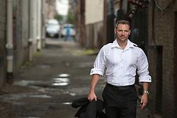 man in a tuxedo shirt walking down an alley in Hoboken, NJ