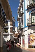 People exploring narrow streets at popular holiday resort town of Nerja, Malaga province, Spain